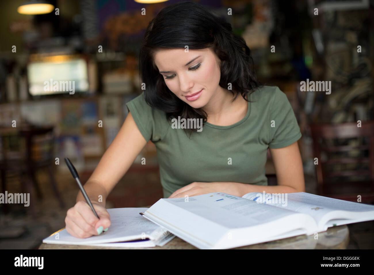 Porträt von Teenager-Mädchen studieren im Kaffeehaus Stockbild