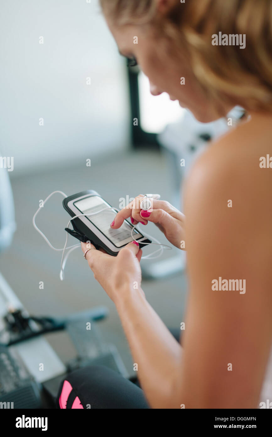 Junge Frau, mit mobilen während des Trainings im Fitnessstudio Stockbild