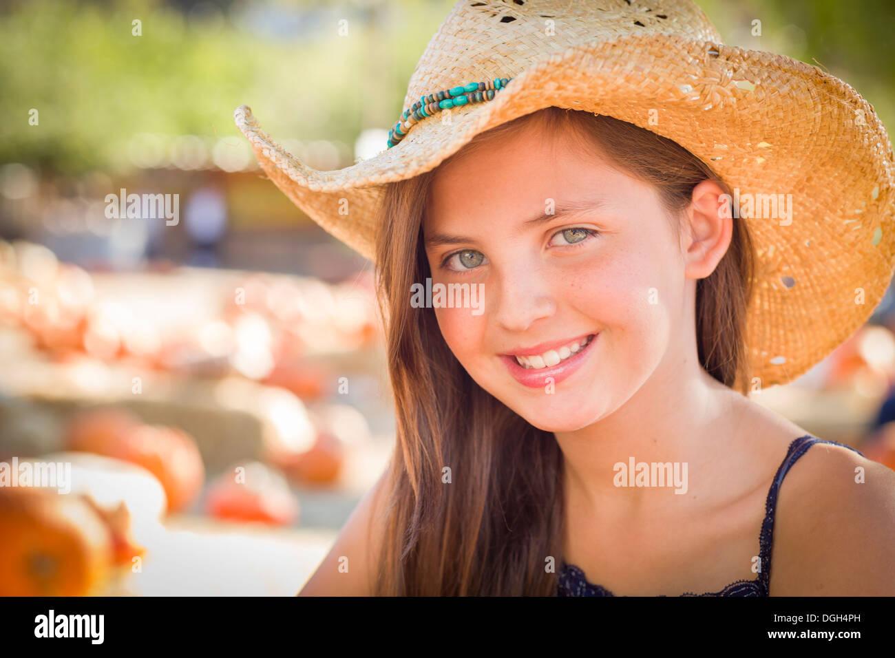 Preteen Mädchen Portrait Cowboy Hut im Kürbisbeet in rustikalem Ambiente. Stockbild