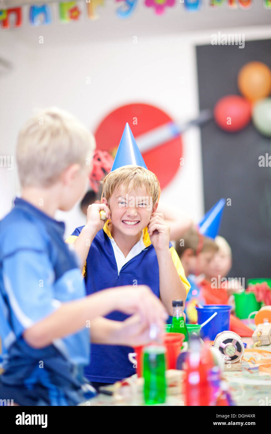 Junge auf Geburtstagsparty mit den Fingern in den Ohren Stockbild