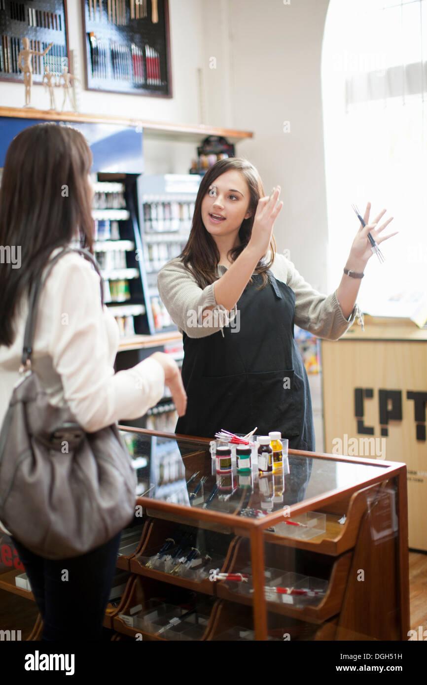 Verkäuferin im Gespräch mit Kunden im Handwerk shop Stockbild