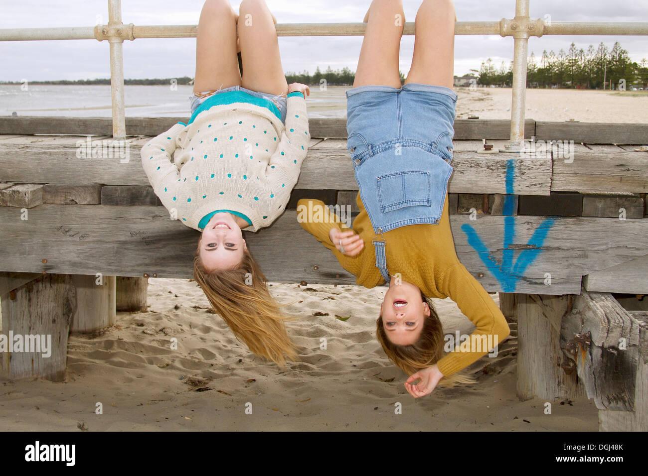 Freundinnen kopfüber vom pier Stockbild