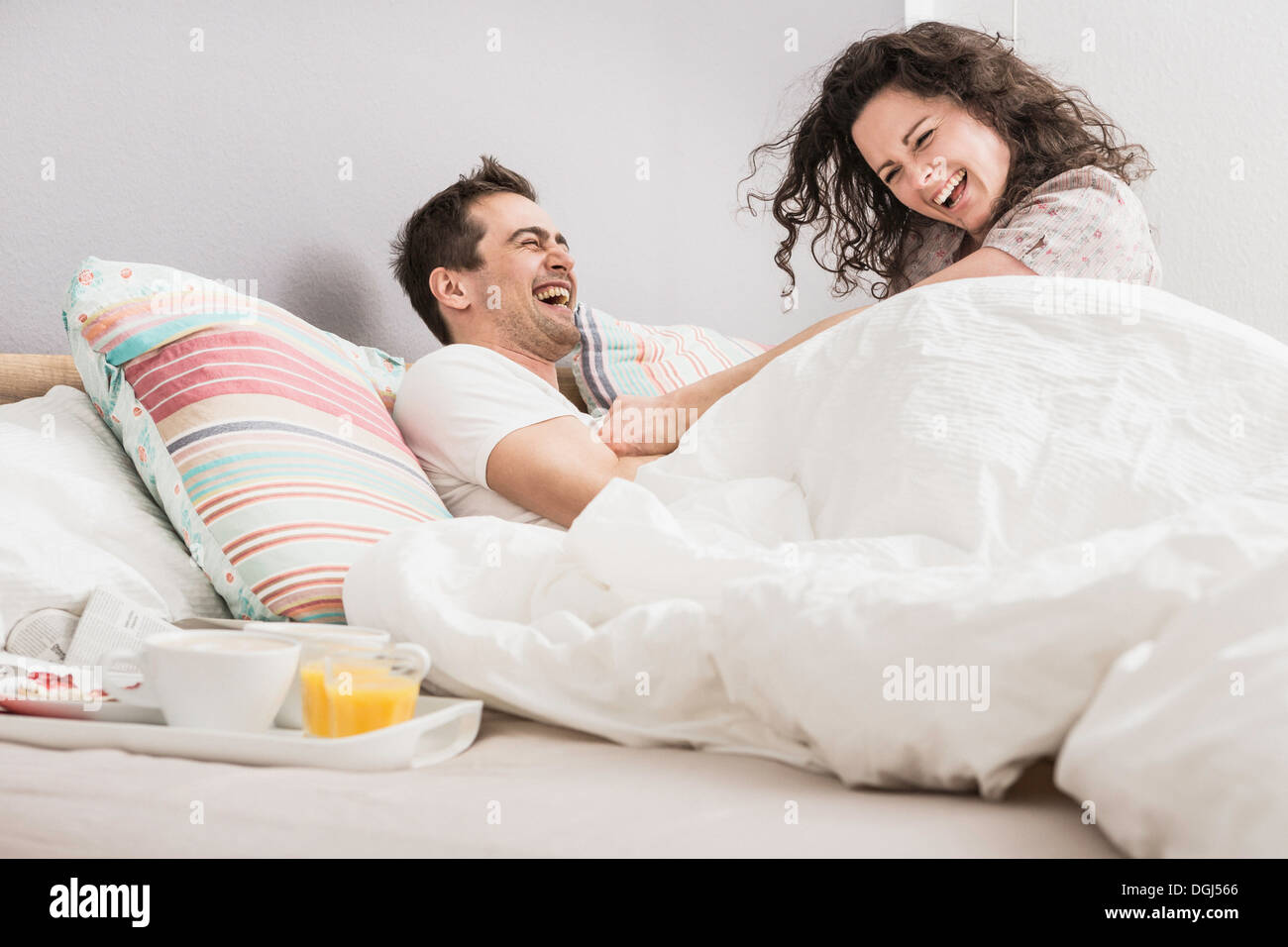 Mitte erwachsenes paar im Bett liegend Frühstück auf Tablett, Kissenschlacht Stockbild