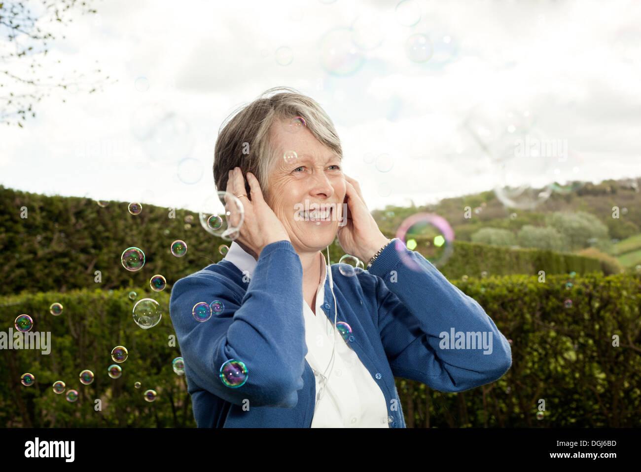 Ältere Frau für Ohren und lachen über Bläschen Stockbild