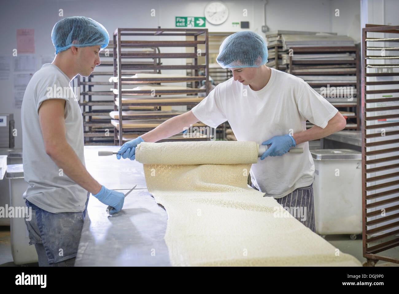 Bäcker in Schutzkleidung, die Länge der Teig vorbereiten Stockbild