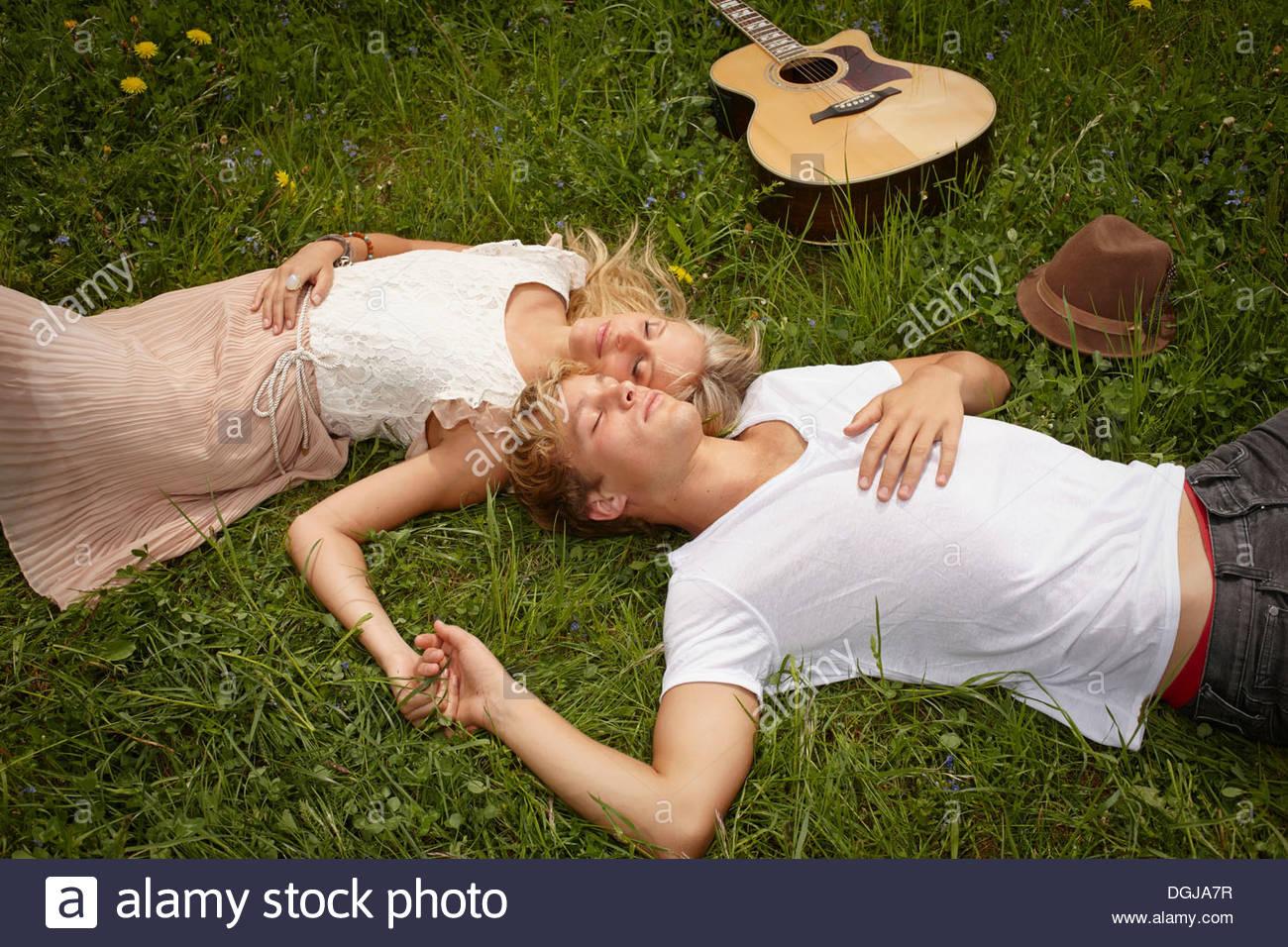 Junges Paar liegen auf dem Rasen mit Augen geschlossen Stockbild