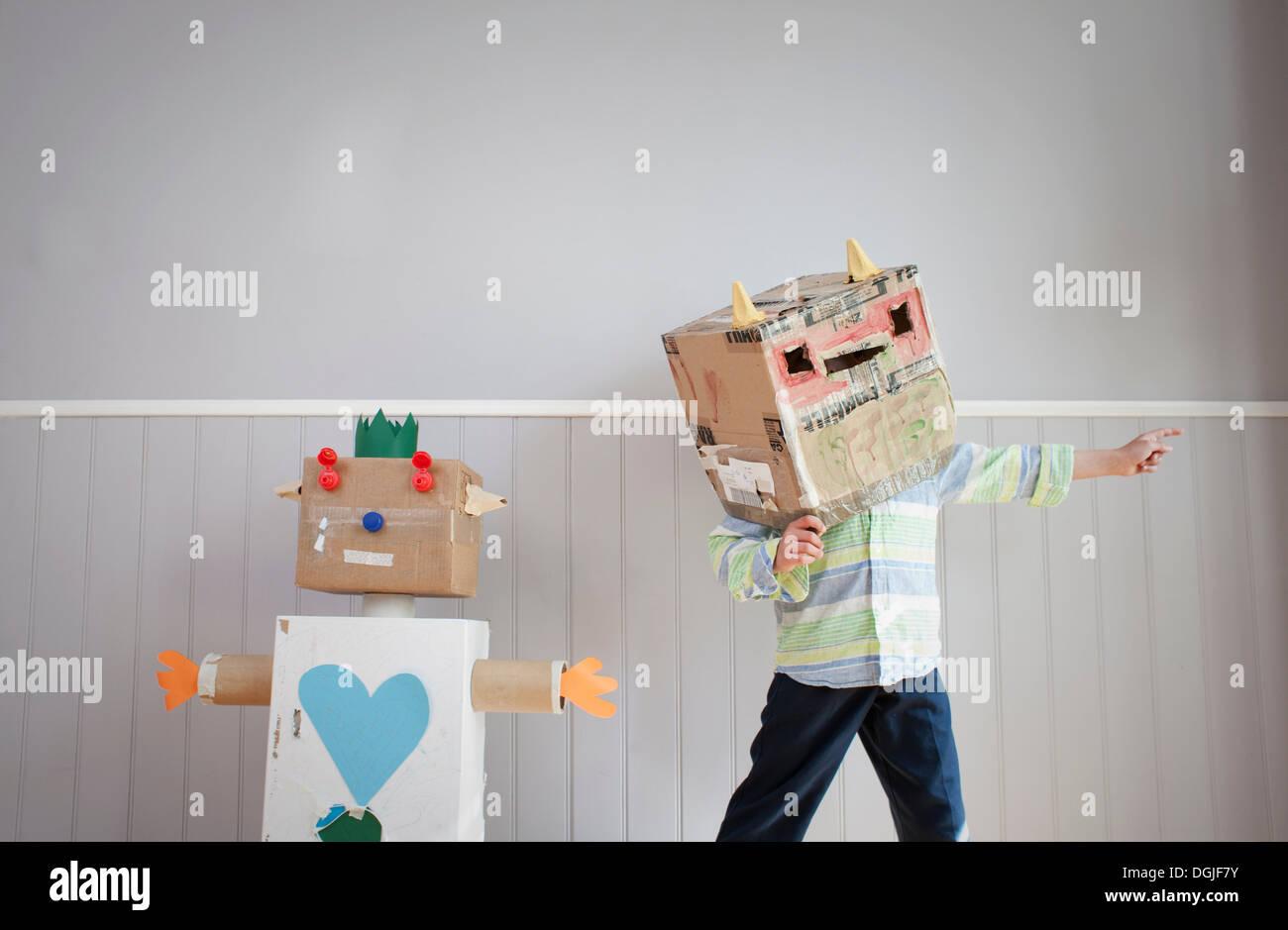 Junge mit Box für Kopf und hausgemachte Spielzeugroboter Stockbild