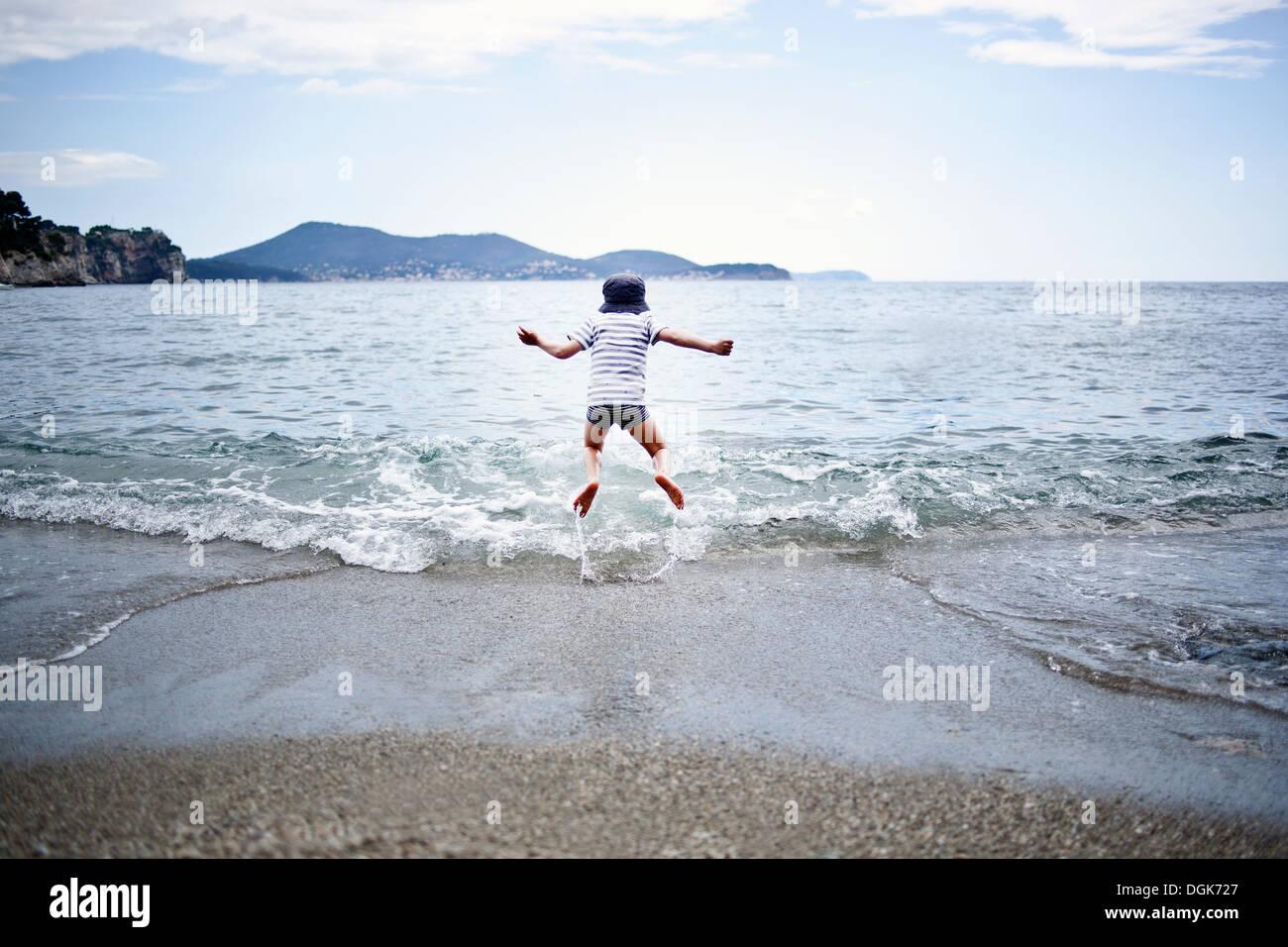 Kleiner Junge springt ins Meer Stockbild
