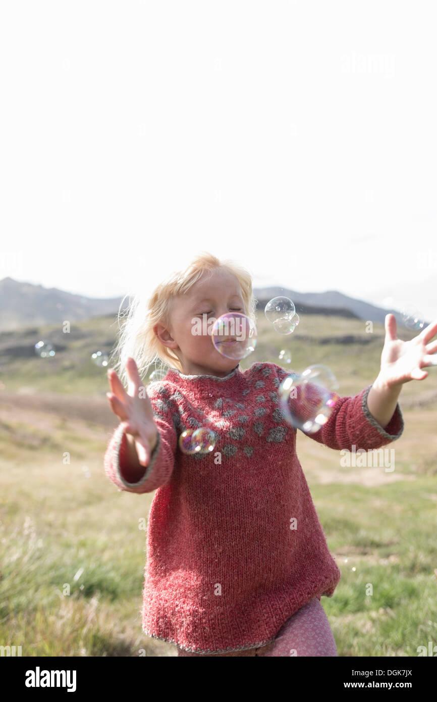 Junges Mädchen mit Augen geschlossen ausgeführt, um Luftblasen zu fangen Stockbild