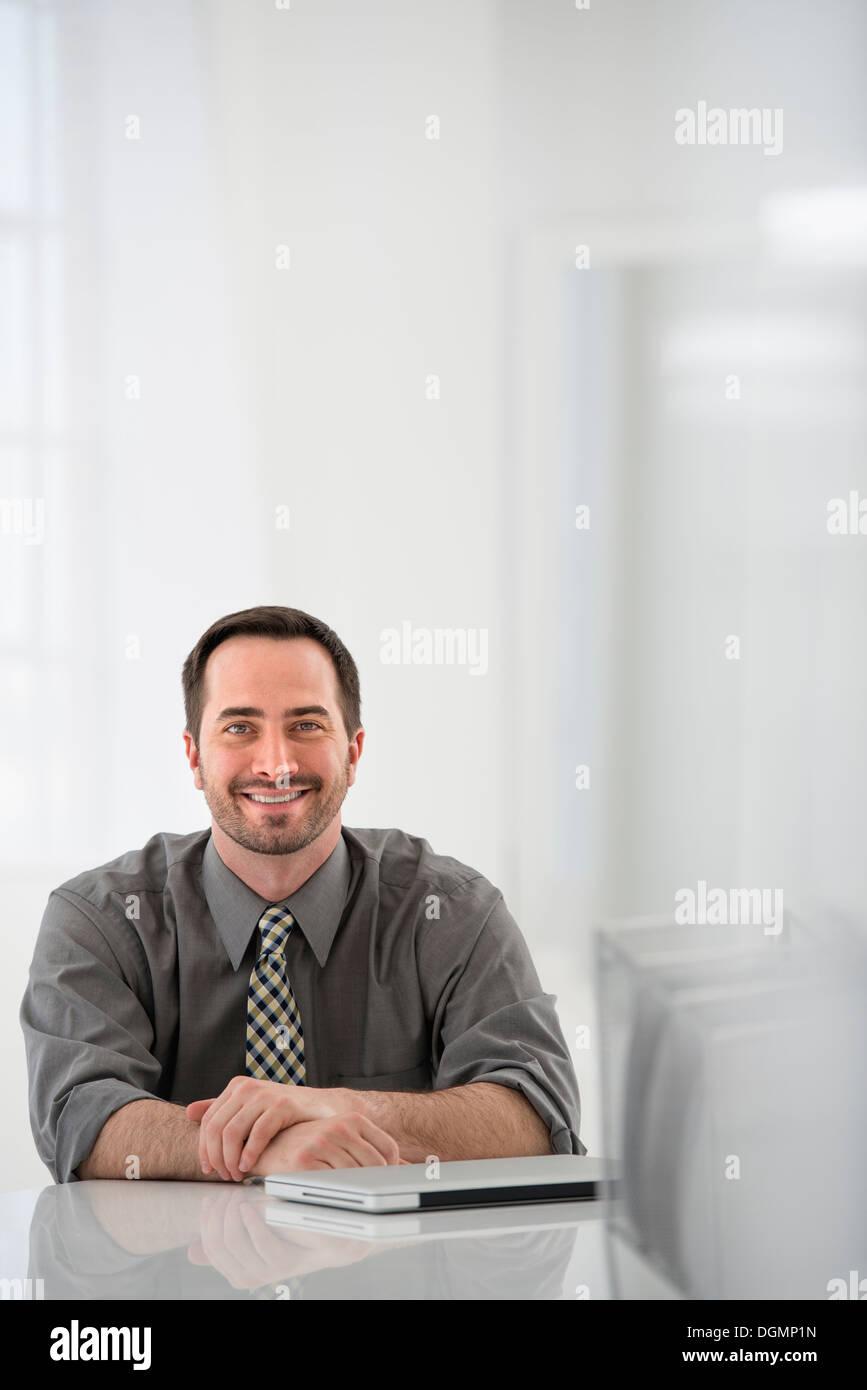 Büroeinrichtung. Ein Mann sitzt an einem Tisch, neben einem geschlossenen Laptop-Computer. Stockbild