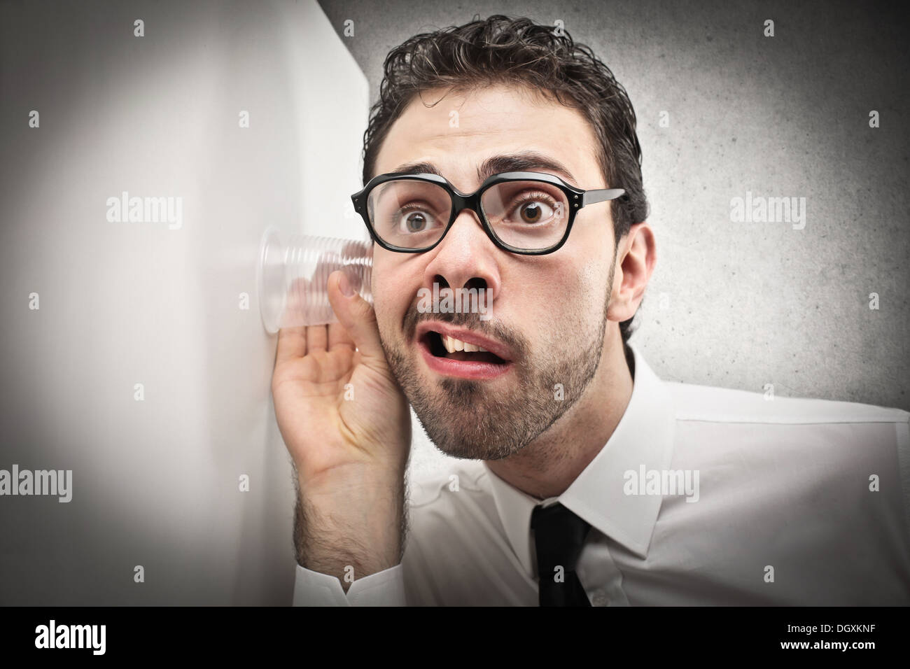 Büroangestellte mit Brille, die versuchen, durch eine Wand zu hören Stockbild