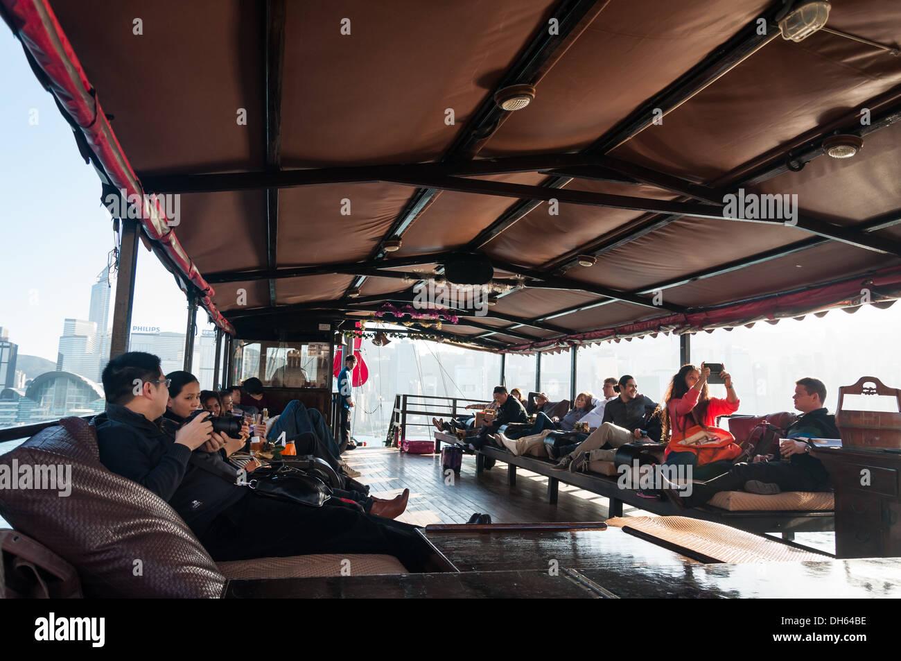 Touristen, die Entspannung an Bord eines traditionellen Junk-Schiffes in Hong Kong. Stockbild