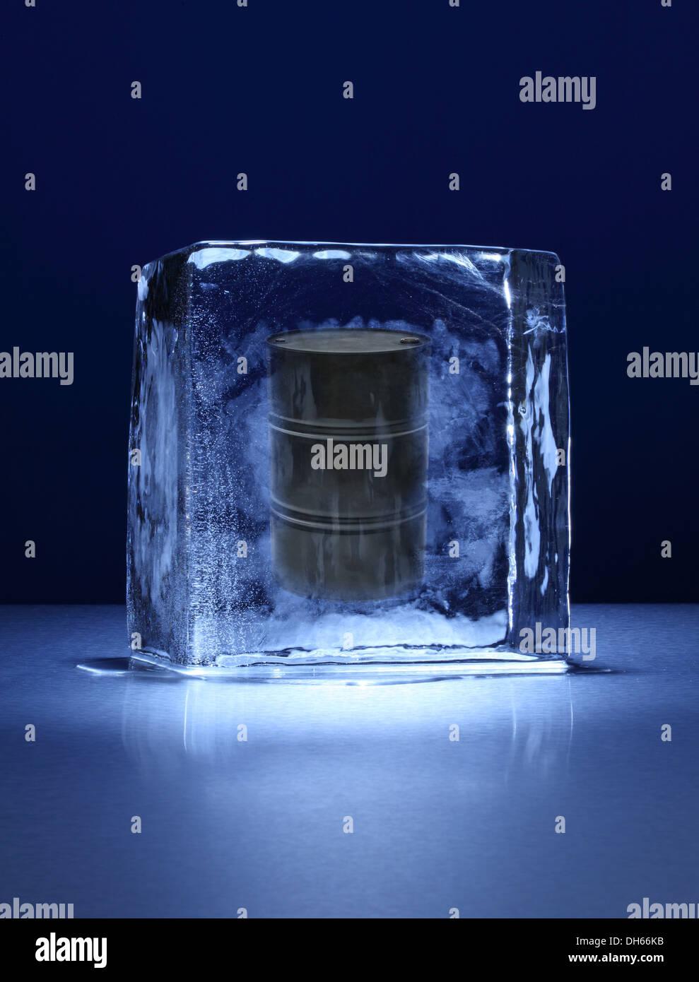 Ein schwarzes Öl-Fass in einem klaren Eisblock eingefroren Stockbild