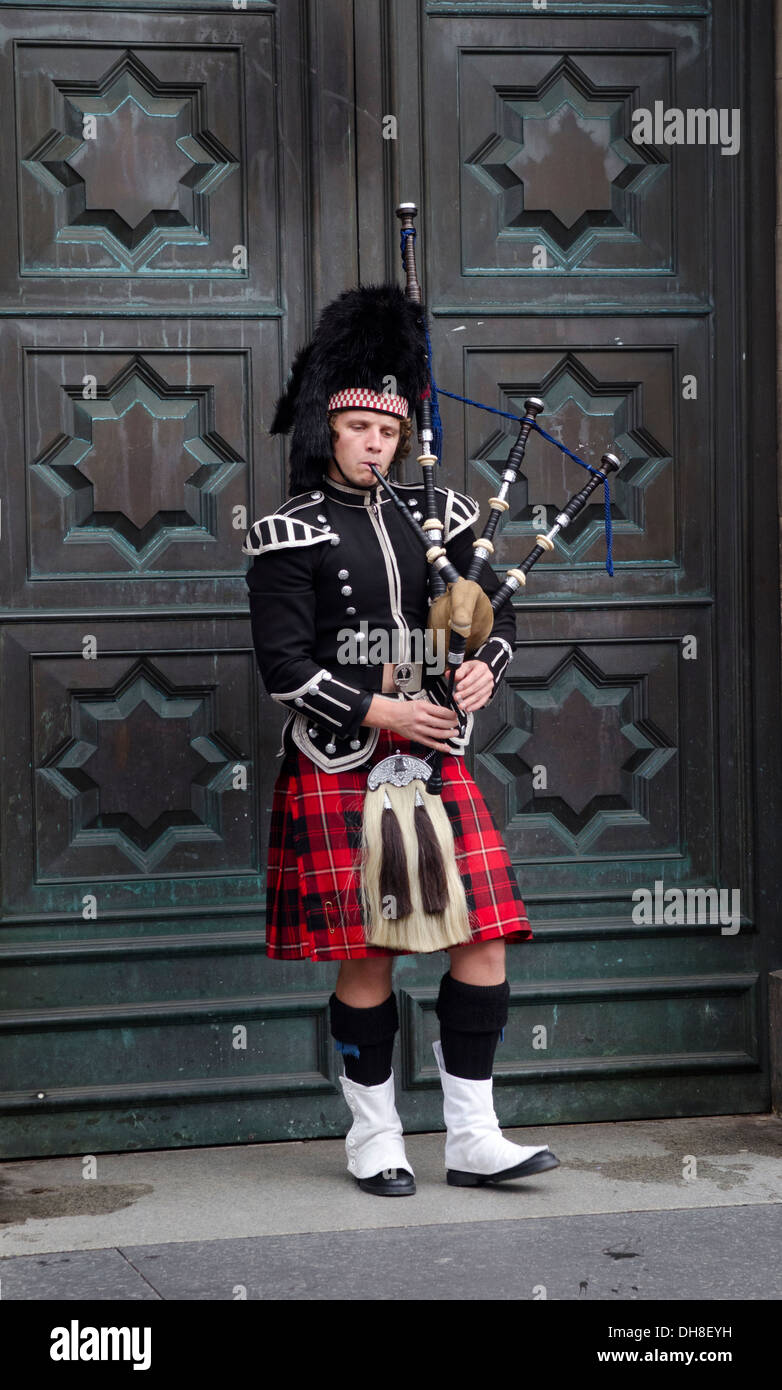 Piper in traditioneller Tracht Dudelsack vor große Tür auf der Royal Mile in Edinburgh Stockbild