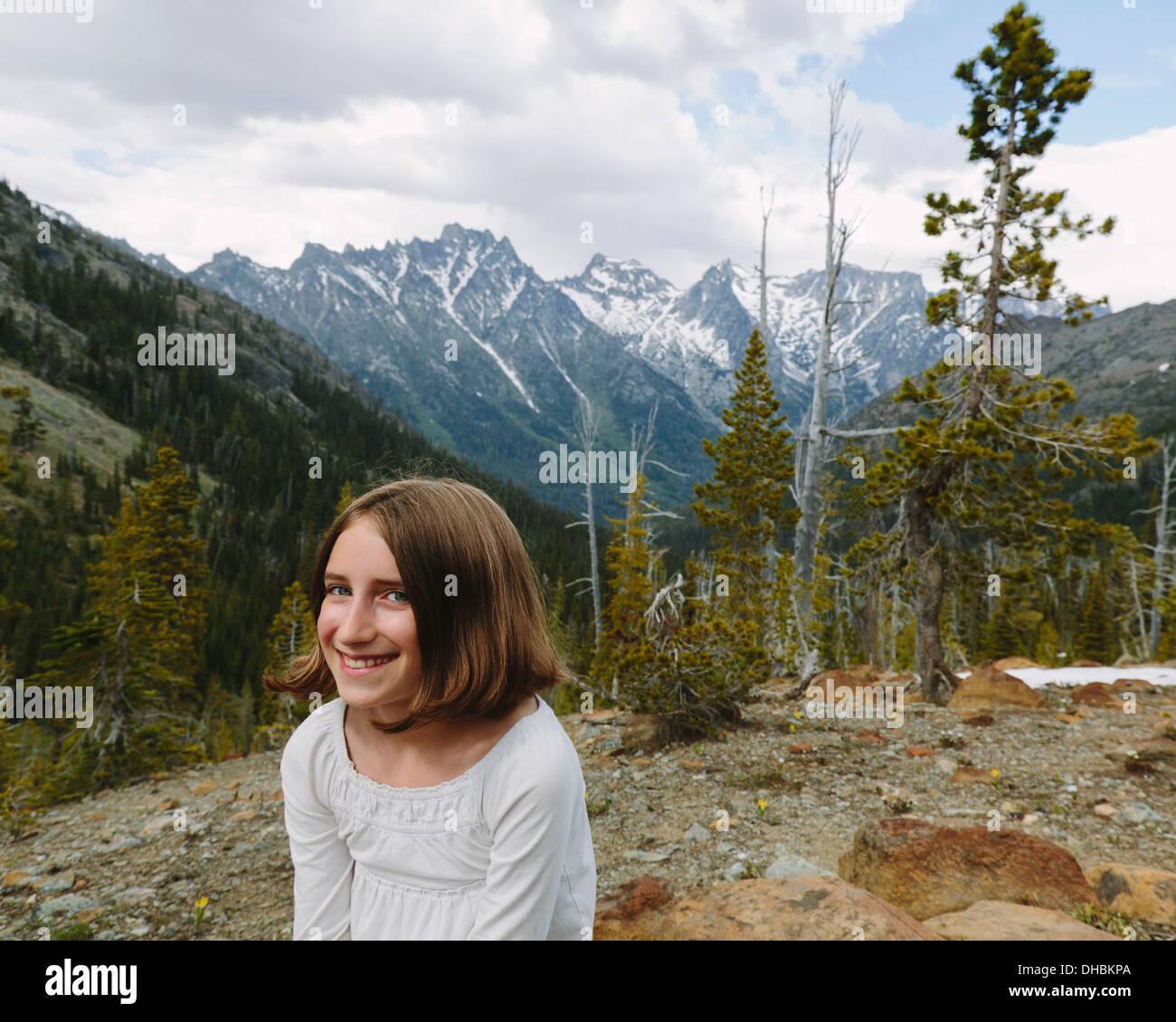 Ein junges Mädchen sitzt an einem Aussichtspunkt mit Blick über die Berge von Wenatchee National Forest. Stockbild