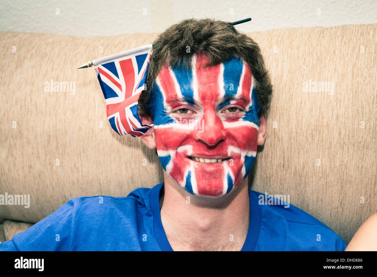 Porträt von lustigen Mann mit britischer Flagge gemalt auf seinem Gesicht. Stockbild