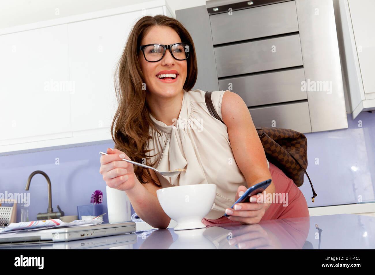 Junge Frau beim Frühstück mit Handy Stockbild