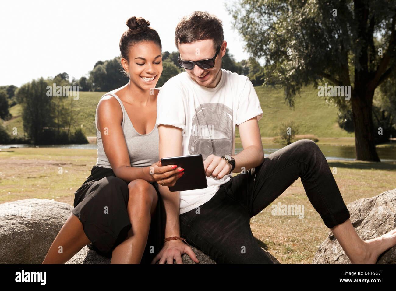 Junges Paar mit digital-Tablette im park Stockbild