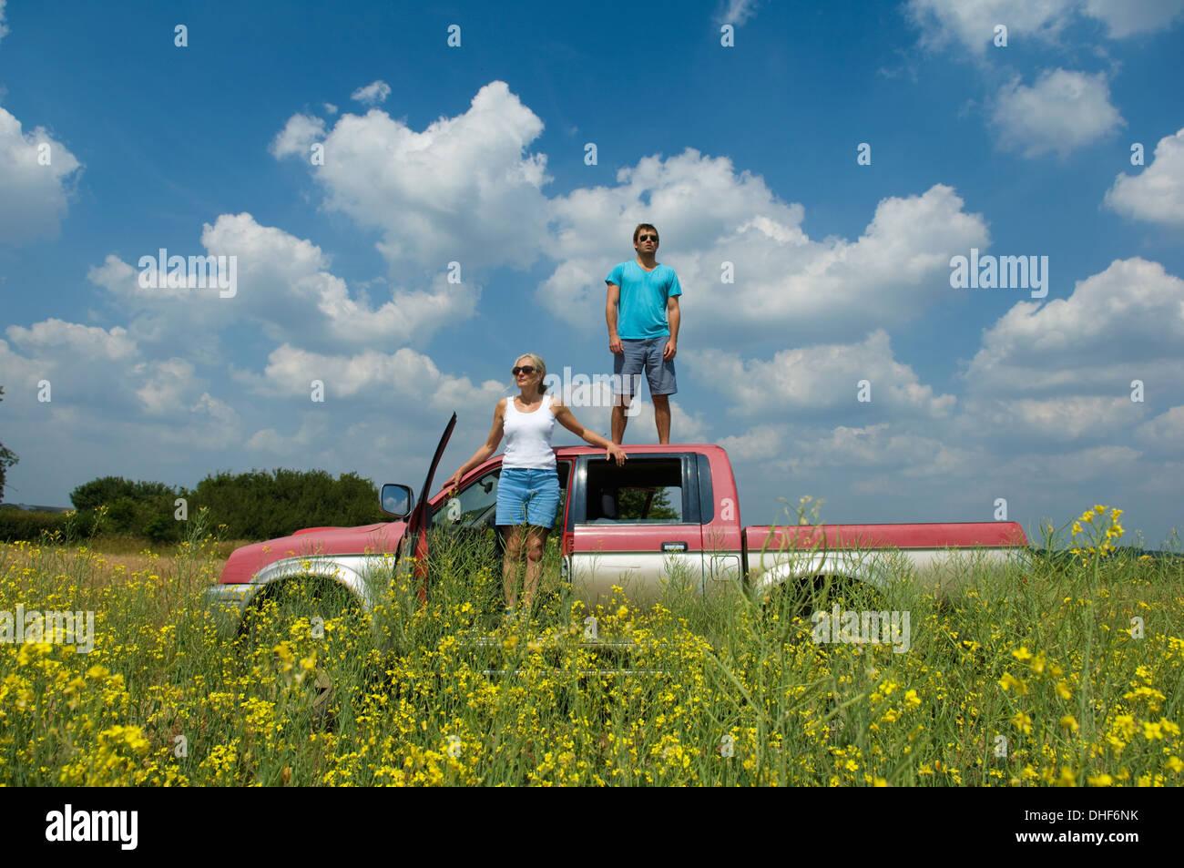 Mutter und Sohn mit Pickup-Truck im Feld, Sohn stand am Anfang von LKW Stockbild