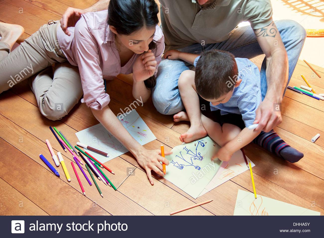 Junge sitzt auf Bodenzeichnung mit Eltern Stockbild