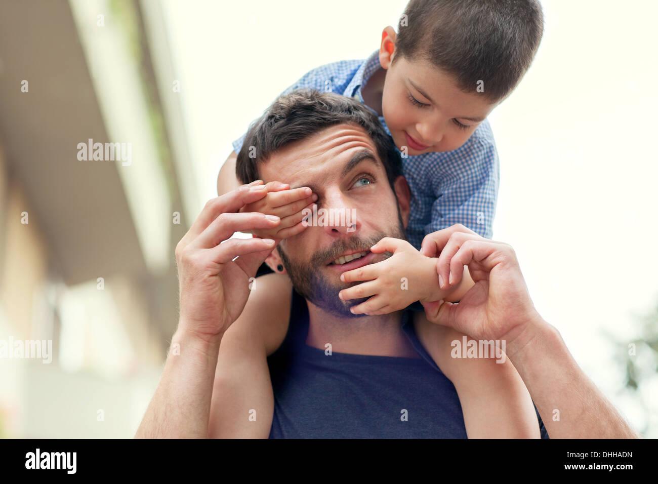 Vater mit Sohn auf Schultern, junge über Mannes Auge Stockbild