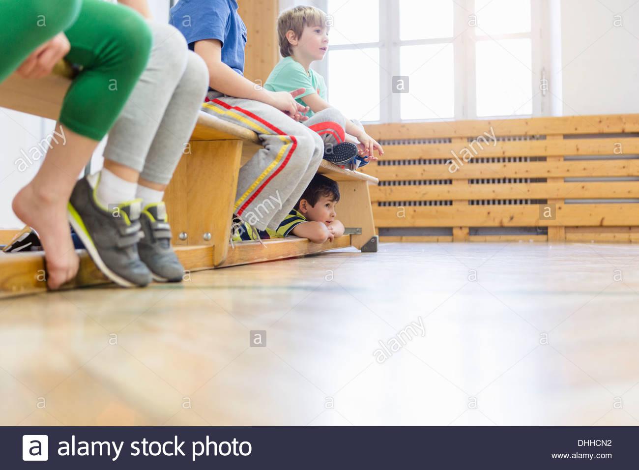 Kinder sitzen auf Bank in Aula, ein Junge unter Stockbild