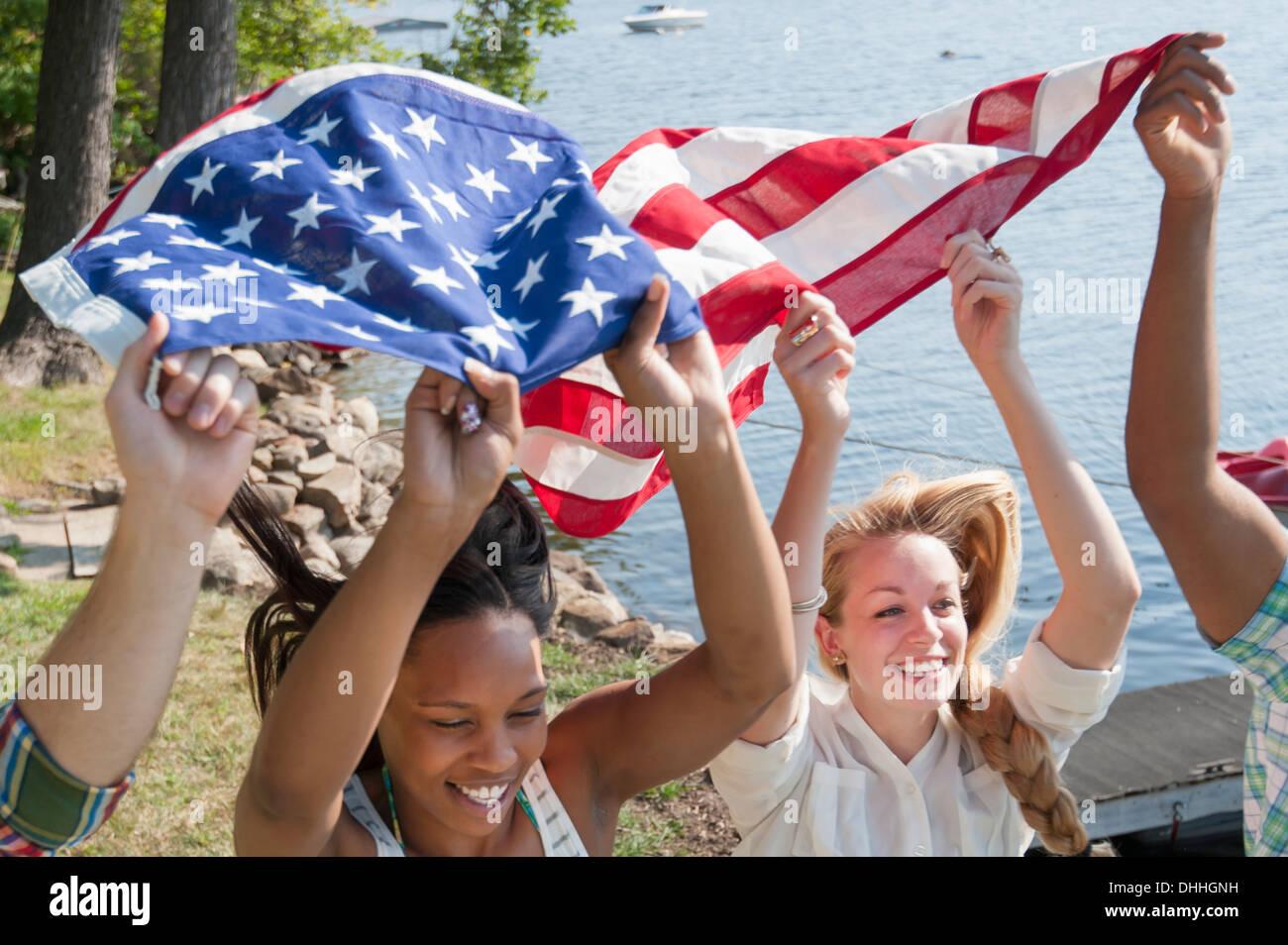 Freunde mit US-Flagge über Köpfen, Lächeln Stockbild