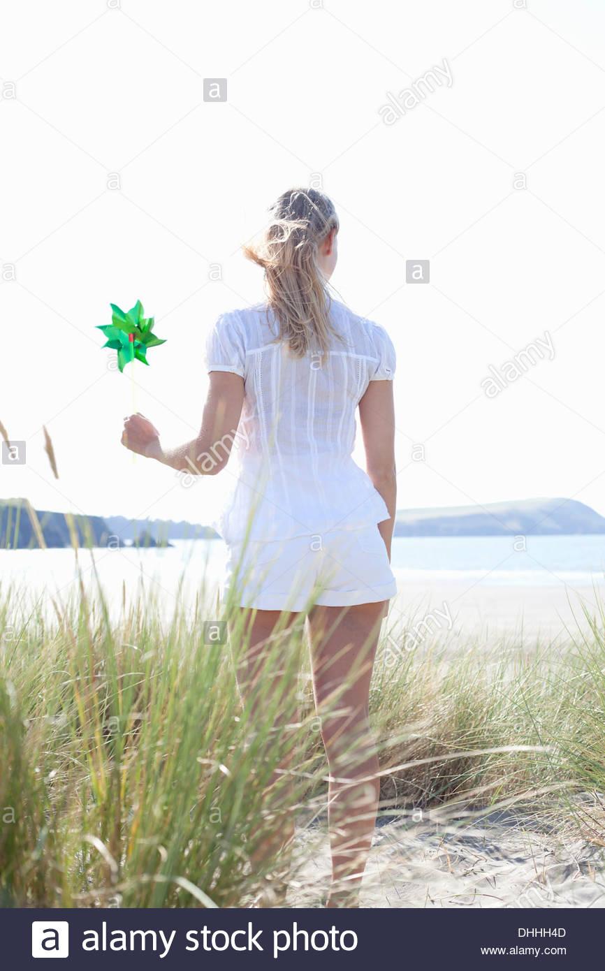 Frau am Strand halten Sie Pin Rad, Rückansicht, Wales, UK Stockbild