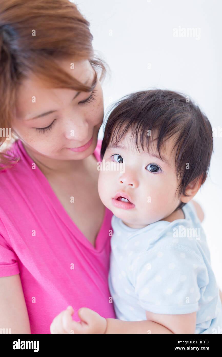Mutter blickte auf Baby in armen Stockbild