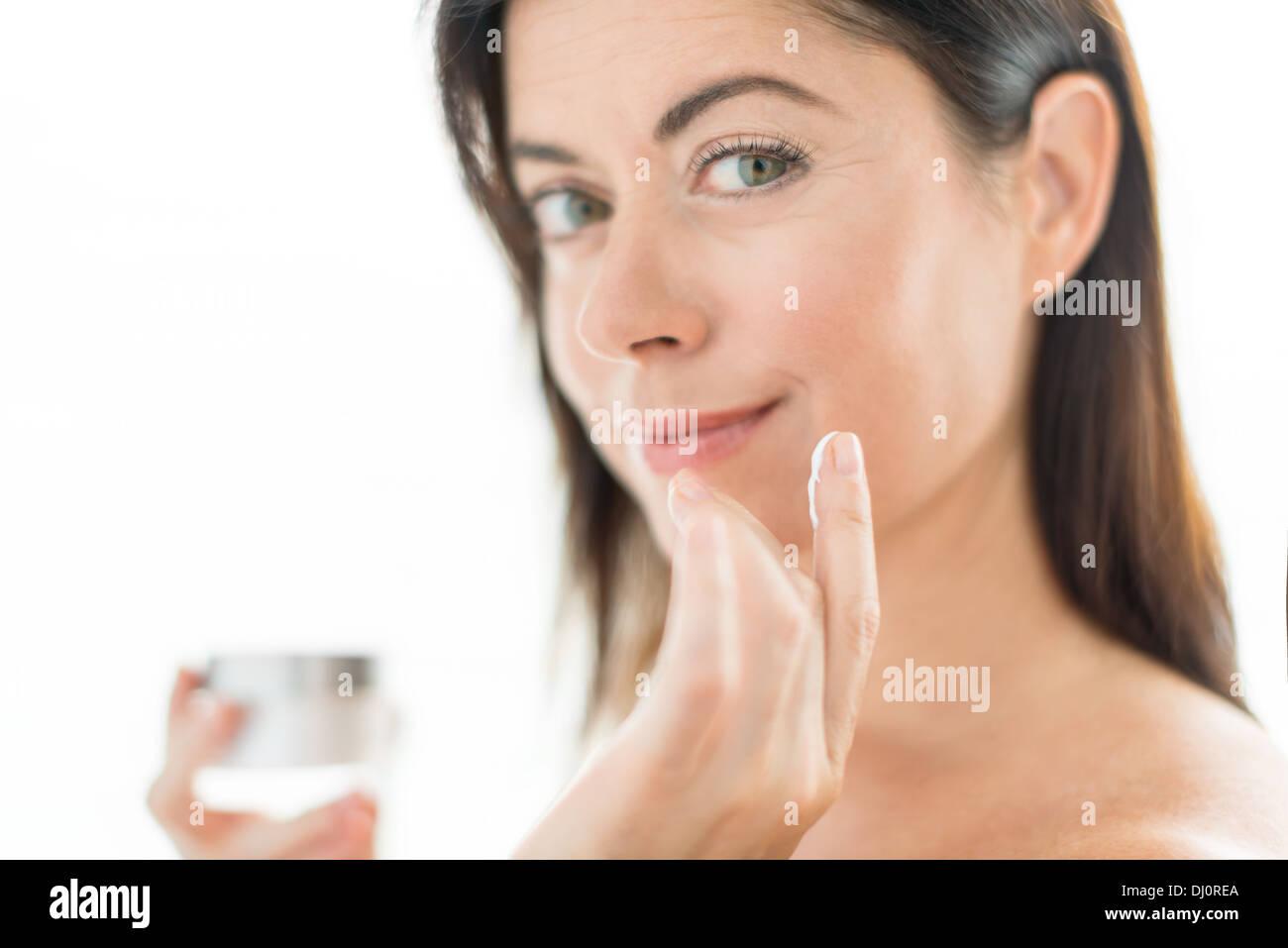 Porträt einer schönen Reife Dame gegen Falten mit einer luxuriösen Gesichtslotion Stockbild