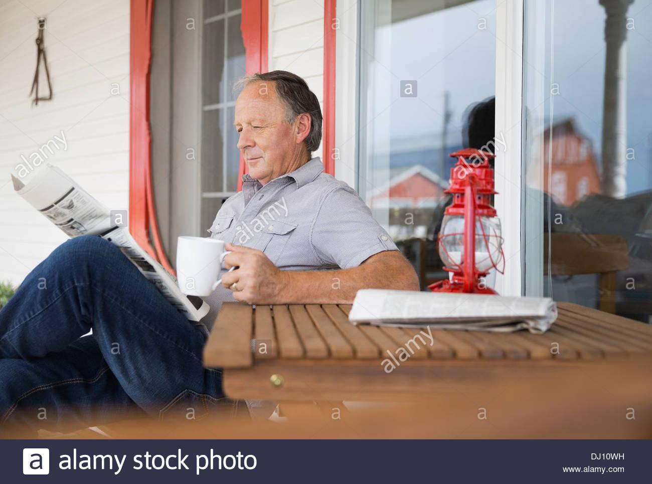 Ältere Mann liest Zeitung mit Kaffee Stockbild