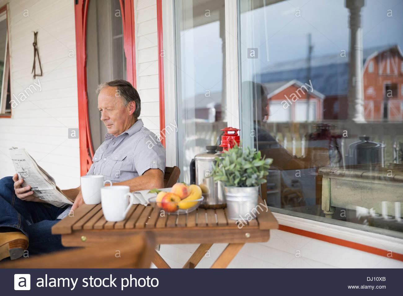 Ältere Mann liest Zeitung auf Veranda Stockbild