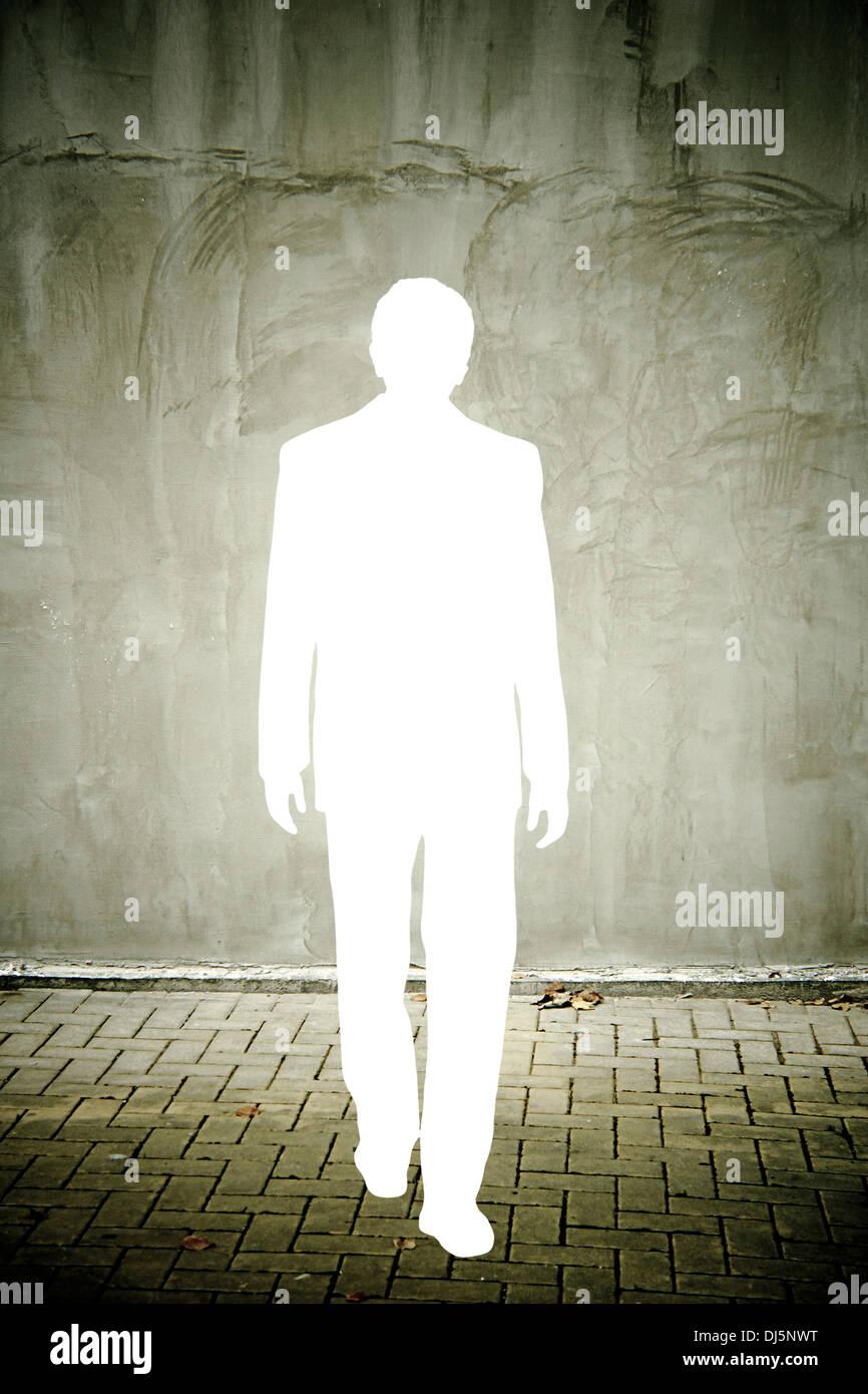 Ausschnitt einer Geschäftsmann Silhouette in einer notleidenden grauen Wand Stockbild
