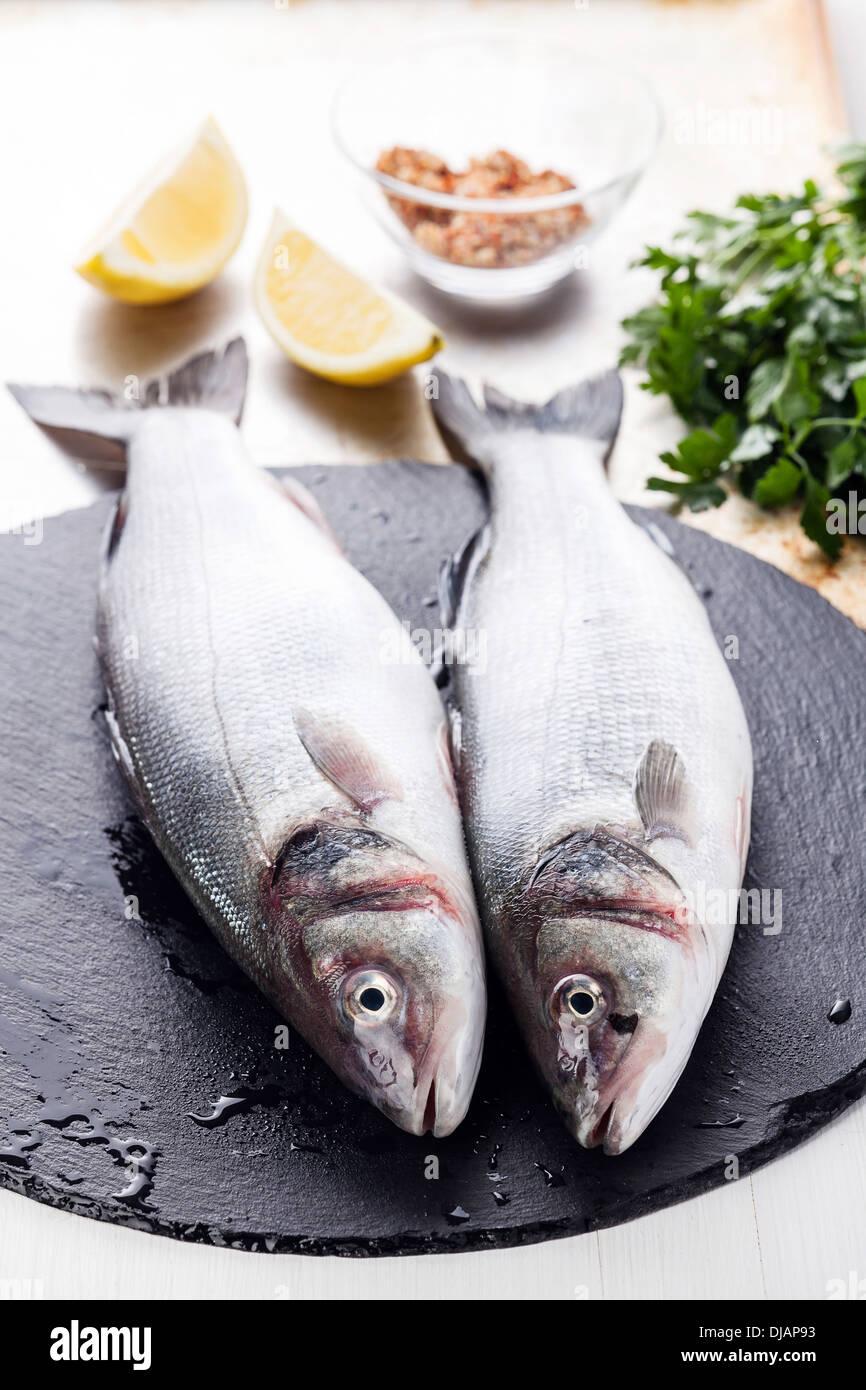 Roher Fisch Wolfsbarsch mit Kräutern und Zitrone auf strukturierten Hintergrund Stockbild