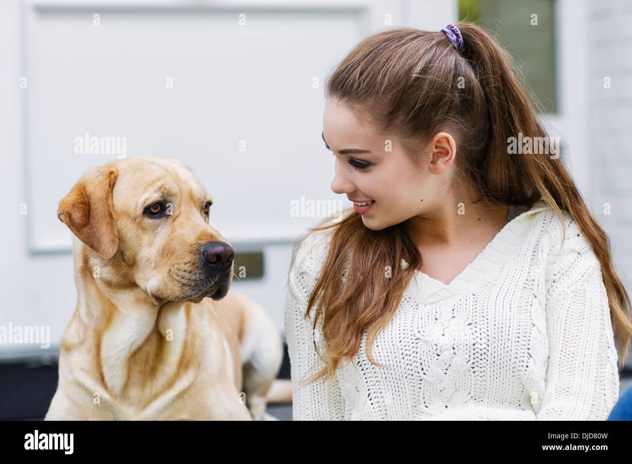Teenager-Mädchen mit Hund sitzt vor einer Eingangstür Stockbild