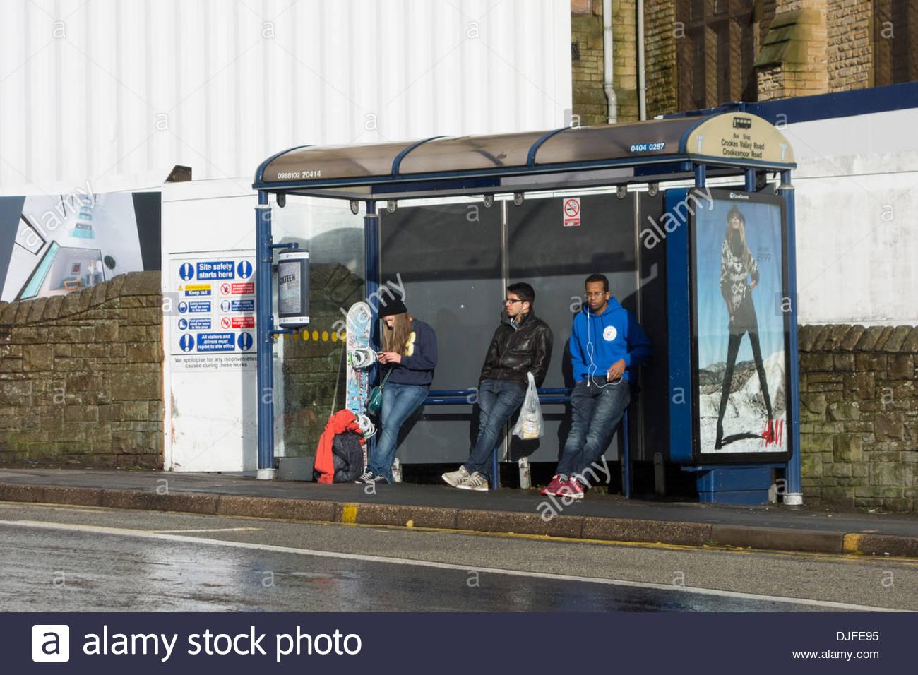 drei menschen warten auf einen bus in einer bushaltestelle. Black Bedroom Furniture Sets. Home Design Ideas