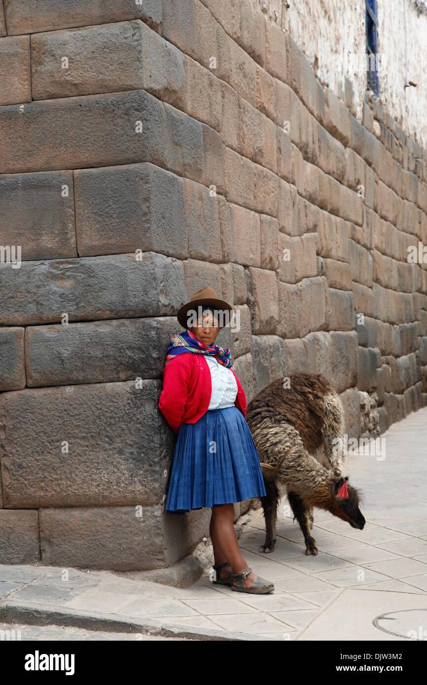 Quechua-Frau mit Lama entlang einer Inka-Wand in San Blas Nachbarschaft, Cuzco, Peru. Stockbild