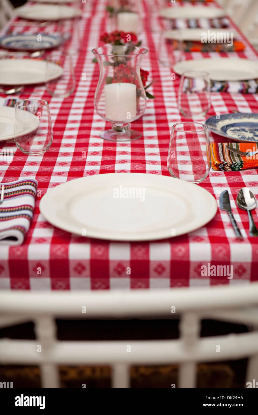 Legen Sie Einstellungen auf rot-weiß karierte Tischdecke Stockbild