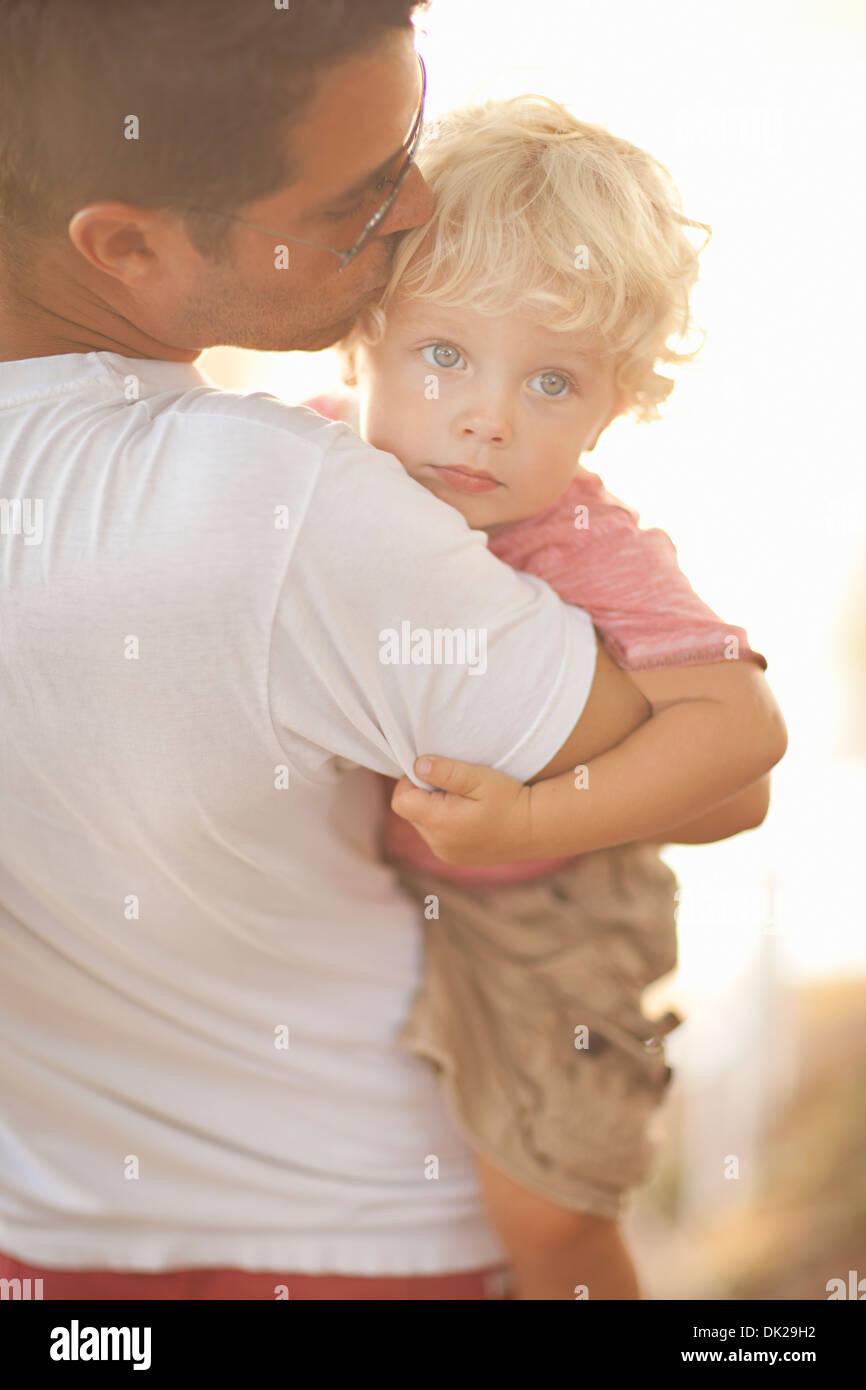 Vater mit kleinen Sohn und beruhigend durch Stirn küssen Stockbild