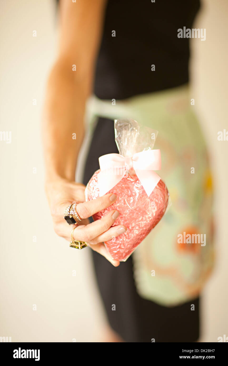 Mittelteil der Frau in Schürze halten eingewickelt Herzform Valentinstag Cookie hautnah Stockbild