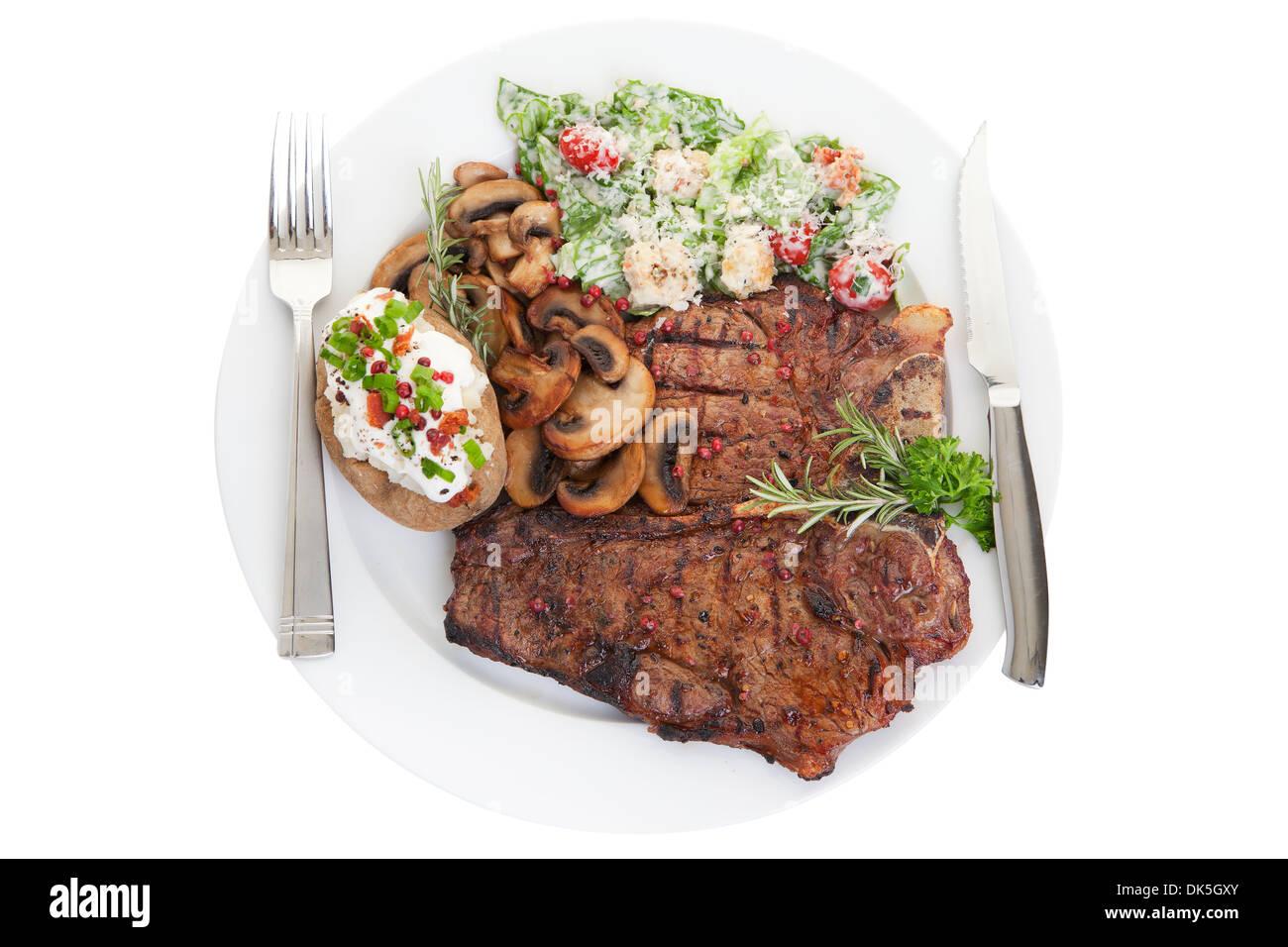 Gegrilltes Rindfleisch t-Bone-Steak-Dinner mit Caesar Salat, Champignons und Rosmarin Stockbild