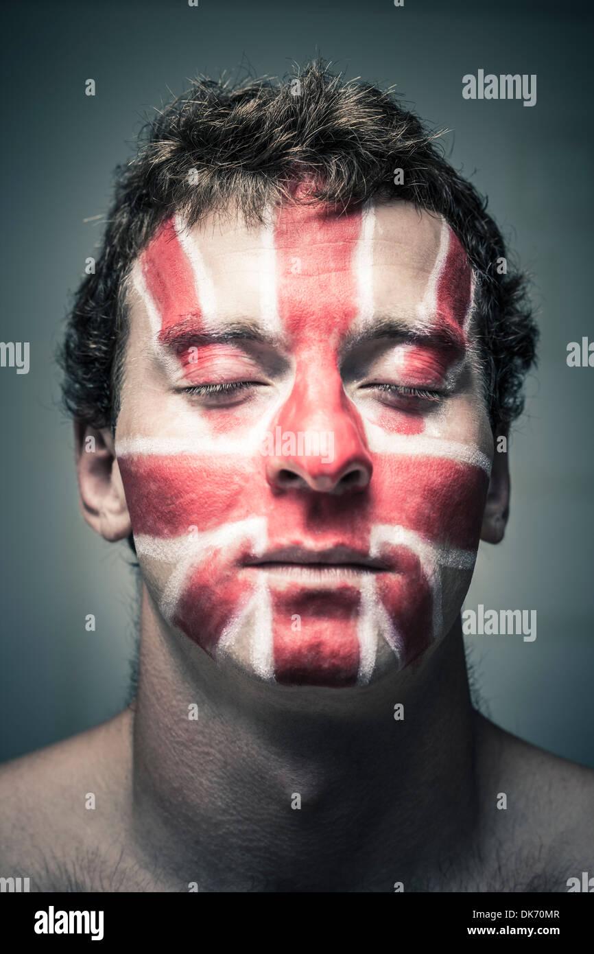 Porträt des Mannes mit britischer Flagge auf seinem Gesicht gemalt und schloss die Augen. Stockbild