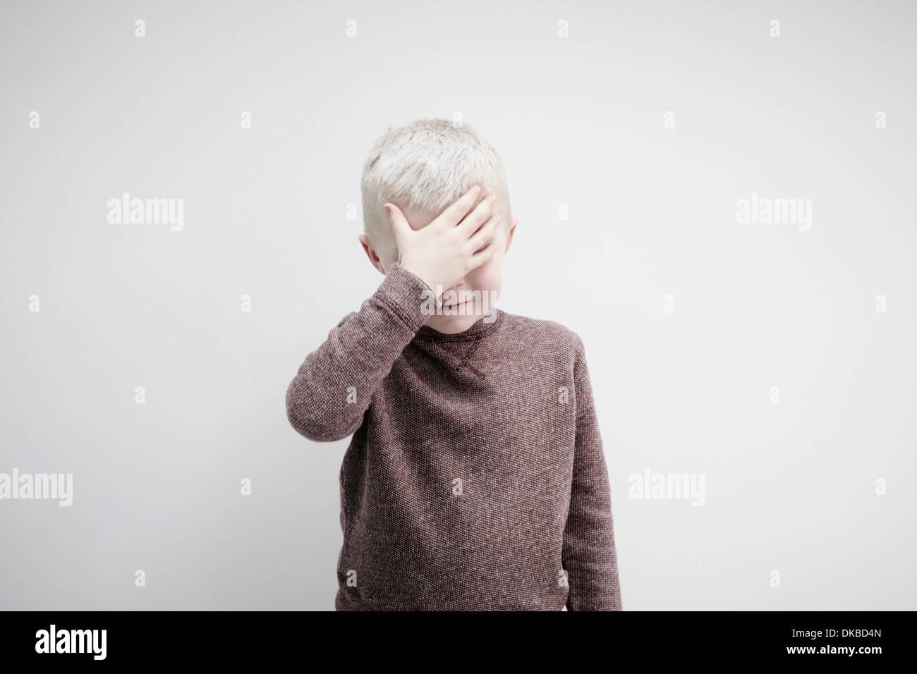 Porträt der jungen tragen braune Jumper für Gesicht mit den Händen Stockbild