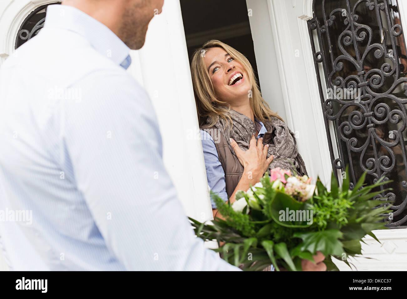 Frau, die Öffnung vorne Foor, Mann mit Blumenstrauß Stockbild