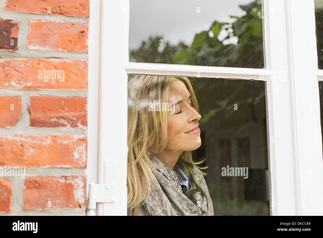 Mitte erwachsenen Frau durch Fenster mit geschlossenen Augen Lächeln Stockbild