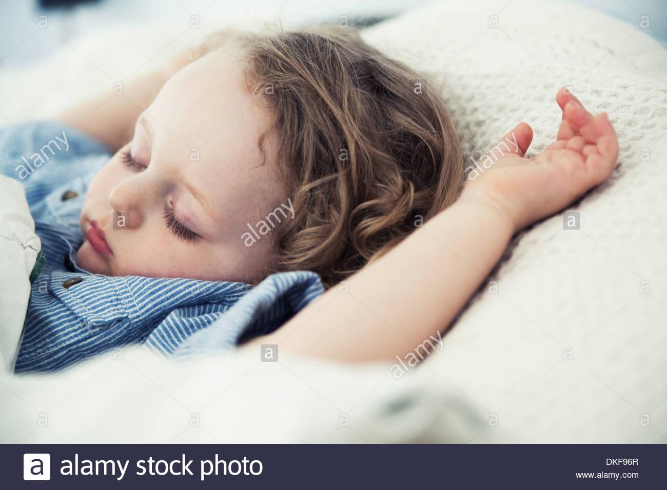 Männliche Kleinkind mit Armen schlafen bis auf Kissen Stockbild