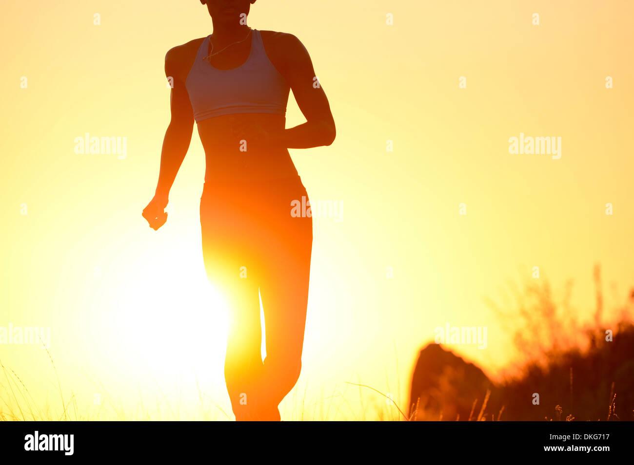 Silhouette der jungen Frau läuft bei Sonnenuntergang Stockbild