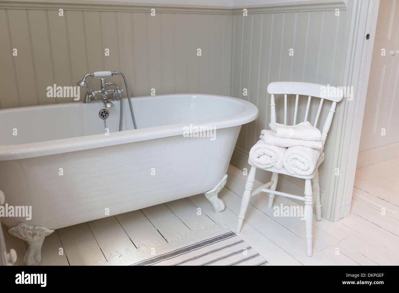 Badewanne und Stuhl im reich verzierten Badezimmer Stockbild