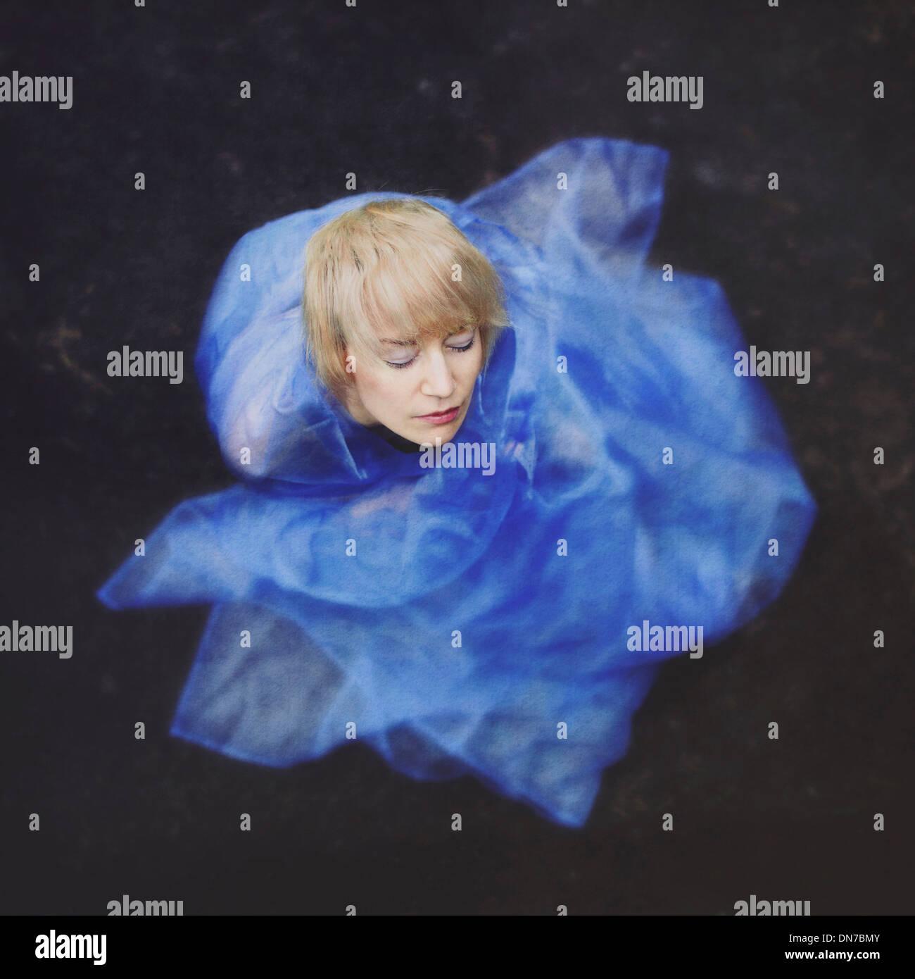 Frau mit geschlossenen Augen in blauem Tuch gewickelt Stockbild
