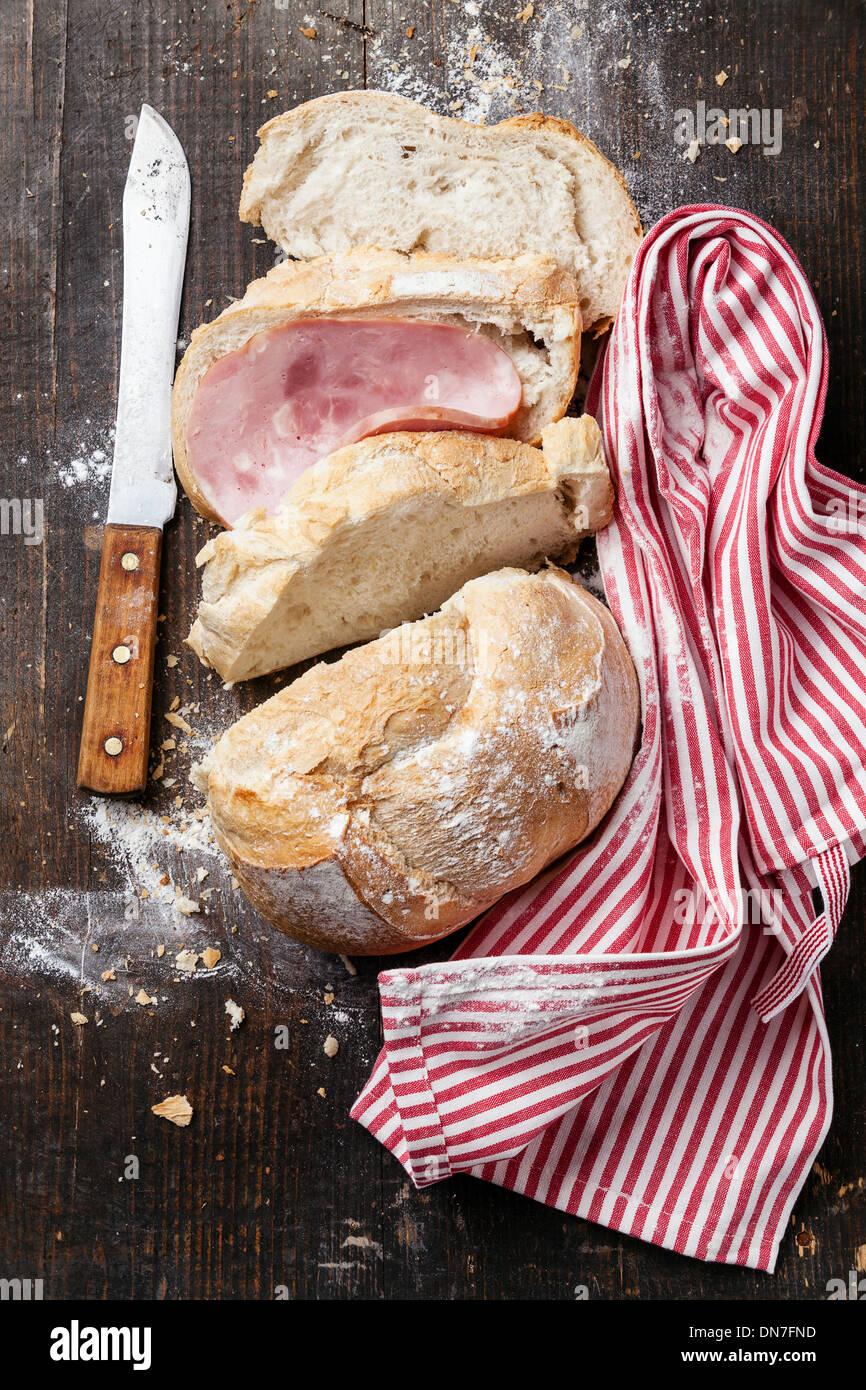 Frisches Baguette mit Schinken auf hölzernen Hintergrund Stockbild